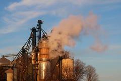 Plan rapproché de dessiccateur de grain avec des poubelles soufflant la vapeur au coucher du soleil photos libres de droits
