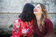 Plan rapproché de deux amis, d'une blonde et de l'autre brune riant grossièrement heureusement image libre de droits