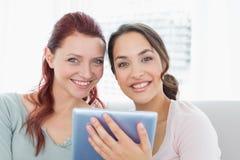 Plan rapproché de deux amis féminins à l'aide du comprimé numérique Images libres de droits