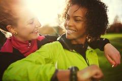 Plan rapproché de deux athlètes féminins étreignant et souriant après séance d'entraînement Photo stock