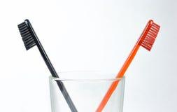 Plan rapproché de deux brosses à dents dans un becher en verre Pour les hommes et des femmes Image stock