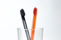 Plan rapproché de deux brosses à dents dans un becher en verre Pour les hommes et des femmes Photo stock