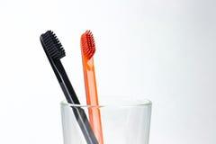 Plan rapproché de deux brosses à dents dans un becher en verre Pour les hommes et des femmes Images stock