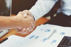 Plan rapproché de deux cadres commerciaux serrant la main aux documents de données sur la table photographie stock libre de droits