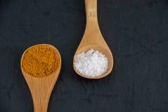 Plan rapproché de deux cuillères en bois avec le cari et le sel brut image stock