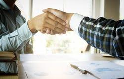 Plan rapproché de deux gens d'affaires se serrant la main tout en se reposant à t Photos libres de droits