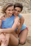 Plan rapproché de deux jeunes femmes souriant sur la plage Image stock