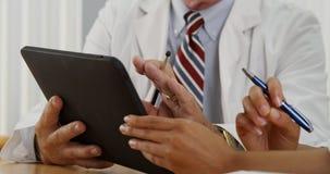 Plan rapproché de deux médecins à l'aide d'un comprimé dans le bureau Images libres de droits
