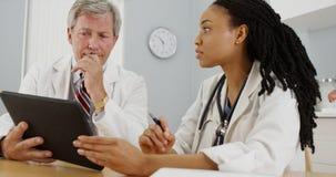 Plan rapproché de deux médecins à l'aide d'un comprimé dans le bureau Photographie stock