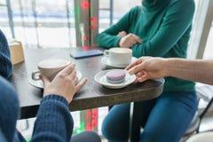Plan rapproché de deux mains de femmes avec des tasses de café et de macarons de plat dans la main de l'homme sur le dessus de ta photos libres de droits