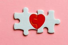 Plan rapproché de deux morceaux d'un puzzle avec le coeur rouge sur le fond rose Photographie stock libre de droits