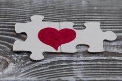 Plan rapproché de deux morceaux d'un puzzle formant un coeur sur une surface en bois rustique, Photo libre de droits