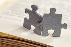 Plan rapproché de deux morceaux de puzzle denteux sur le livre Photo libre de droits