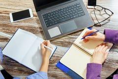 Plan rapproché de deux paires de mains du ` s de femmes dans une vue supérieure de bureau Ordinateur portable, verres, smartphone Photos stock