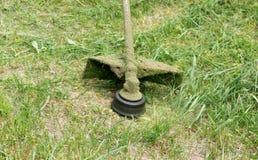 Plan rapproché de faucheuse fauchant l'herbe verte photo stock