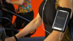 Plan rapproché de femme avec la formation de courroie de bras de smartphone sur le tapis roulant de gymnase banque de vidéos