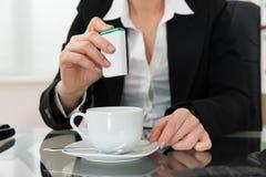 Plan rapproché de femme d'affaires Putting Sugar In Cup images libres de droits