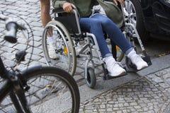 Plan rapproché de femme dans le fauteuil roulant aux étapes du trottoir Photo stock
