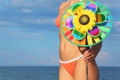 Plan rapproché de femme dans le jouet de pinwheel de fixation de bikini photographie stock