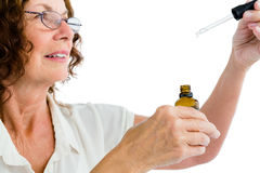 Plan rapproché de femme mûre tenant le compte-gouttes avec la médecine Photos libres de droits