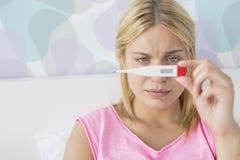 Plan rapproché de femme malade prenant la température avec le thermomètre dans le lit Image stock