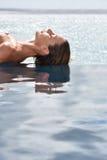 Plan rapproché de femme prenant un bain de soleil par la piscine d'infini Image libre de droits