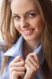 Plan rapproché de femme tenant le collier bleu de chemise Photos stock