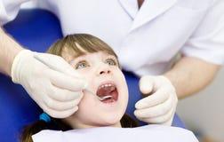 Plan rapproché de fille ouvrant le sien bouche au loin pendant l'inspection photographie stock libre de droits