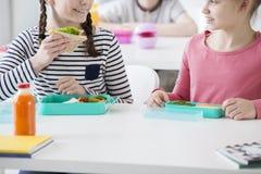 Plan rapproché de fille de sourire mangeant du pain grillé d'eco pendant la coupure de petit déjeuner à l'école Photos stock