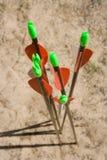 Plan rapproché de flèches de proue de tir à l'arc sur le sable Photos stock