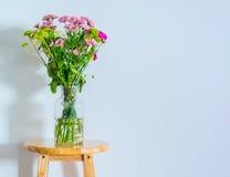 Plan rapproché de fleur rose dans le vase en verre sur la table Photo stock