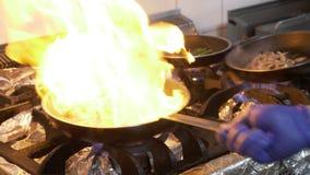 Plan rapproché de fourneau avec la casserole et le chef faisant cuire ajoutant l'huile d'olive et flambant le mélange des légumes clips vidéos