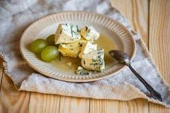 Fromage et raisins bleue d'un plat Images stock