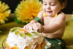 Plan rapproché de gâteau d'écrasement de mains de bébé Images stock