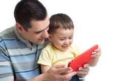 Plan rapproché de garçon d'enfant se reposant avec le père et à l'aide du téléphone portable d'isolement sur le fond blanc Photos stock