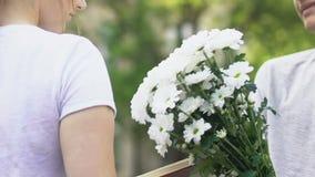 Plan rapproché de garçon de l'adolescence donnant des fleurs à la fille, passion d'offre première dans l'adolescence clips vidéos