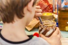 Plan rapproché de garçon préparant le sandwich doux avec du chocolat Photographie stock libre de droits