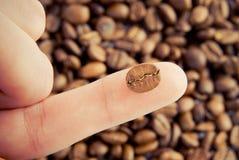 Plan rapproché de grain de café sur le doigt humain Image libre de droits