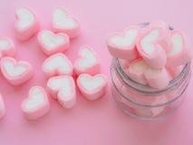 Plan rapproché de guimauve douce sous forme de coeur dans le pot sur le fond rose Photos libres de droits