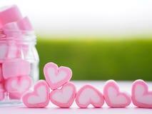 Plan rapproché de guimauve douce sous forme de coeur de plat et de fleur en bois au fond Image stock