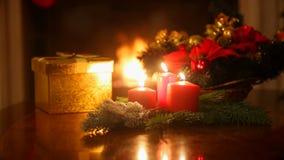 Plan rapproché de guirlande de Noël avec trois bougies rouges brûlantes Lumières colorées rougeoyantes Blurred sur le fond banque de vidéos