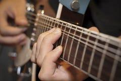 Plan rapproché de guitare électrique avec des doigts le jouant Image libre de droits