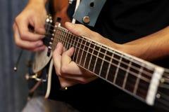 Plan rapproché de guitare électrique avec des doigts le jouant Photos stock