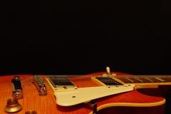 Plan rapproché de guitare électrique de corps solide sur le fond noir, avec l'abondance de l'espace de copie Photo libre de droits
