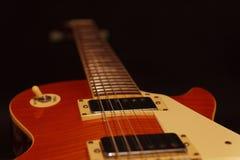 Plan rapproché de guitare électrique de corps solide sur le fond noir Foyer sélectif Images stock