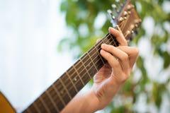 Plan rapproché de guitare acoustique de jeu Fretboard de guitare avec la main masculine photos stock