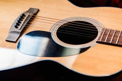 Plan rapproché de guitare acoustique sur le fond foncé Photos stock