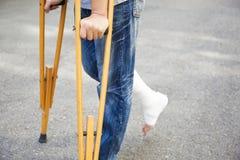 Plan rapproché de jambe sur le bandage avec des béquilles photo stock
