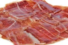 Plan rapproché de jambon espagnol de serrano sur le fond blanc Image libre de droits