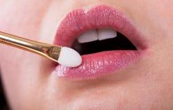 Jeune femme appliquant le maquillage sur des lèvres Photo stock
